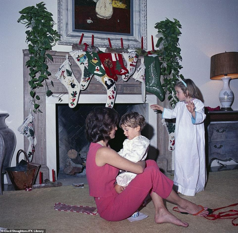 7433814-6497033-Jacqueline_Kennedy_holds_her_youngest_son_John_F_Kennedy_Jr_with-a-4_1545748946255.jpg