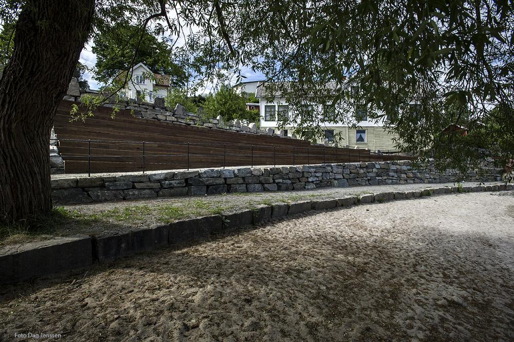 Turvegen vert sleppt ned mellom sittetrappene i tre og den nye natursteinsmuren mot badestranda. Mot den øvre plassen ved Landhandelen har vi vidareført dei tradisjonelle stabbesteinane