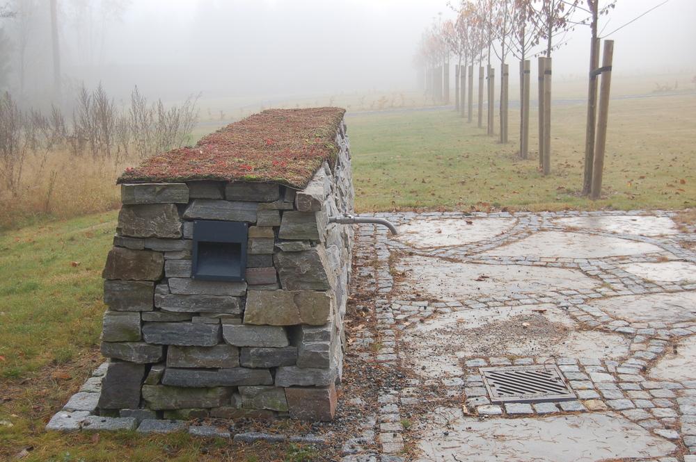 Vannposter og belysning er knyttet til natursteinsmurene. Ved vannpostene er det lagd små plasser med skiferheller som gulv