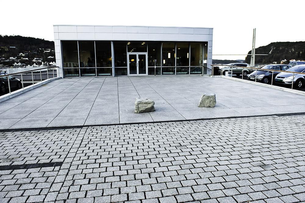 Byggets inngangsparti med granittheller på plassen. Grenlandsbrua i bakgrunnen. Foto: Dag Jenssen