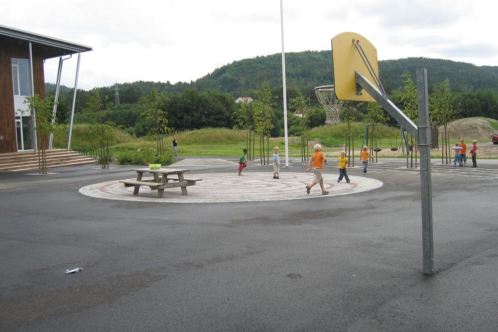 Labyrint og basketkurver i skolegården. Grønne høyder i bakgrunnen