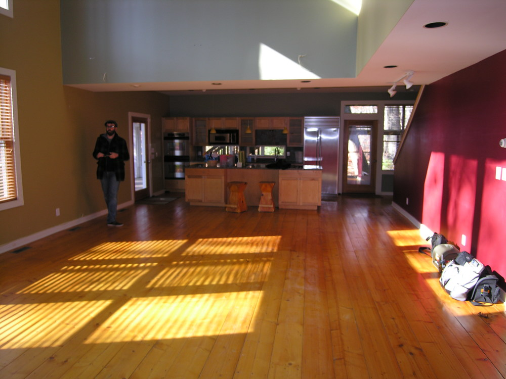 BEFORE: This is the view while standing at the fireplace.  The kitchen is opposite the fireplace, and the ceiling drops in that area.  The varying ceiling heights are perfect for making the eventual sitting area more impressive, however the heavy colors on the walls feel sporadic and closed in.