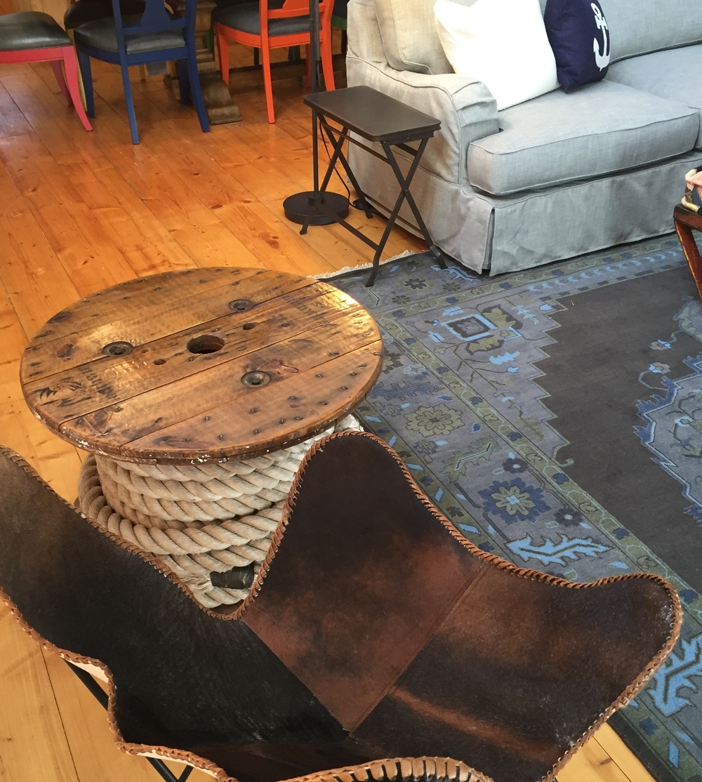 This rope spool was found on an old tug boat in Wisconsin.  The metal framed modern chair is made from rich brown hide and leather.  Layering multiple textures is an easy trick to add depth to your design.