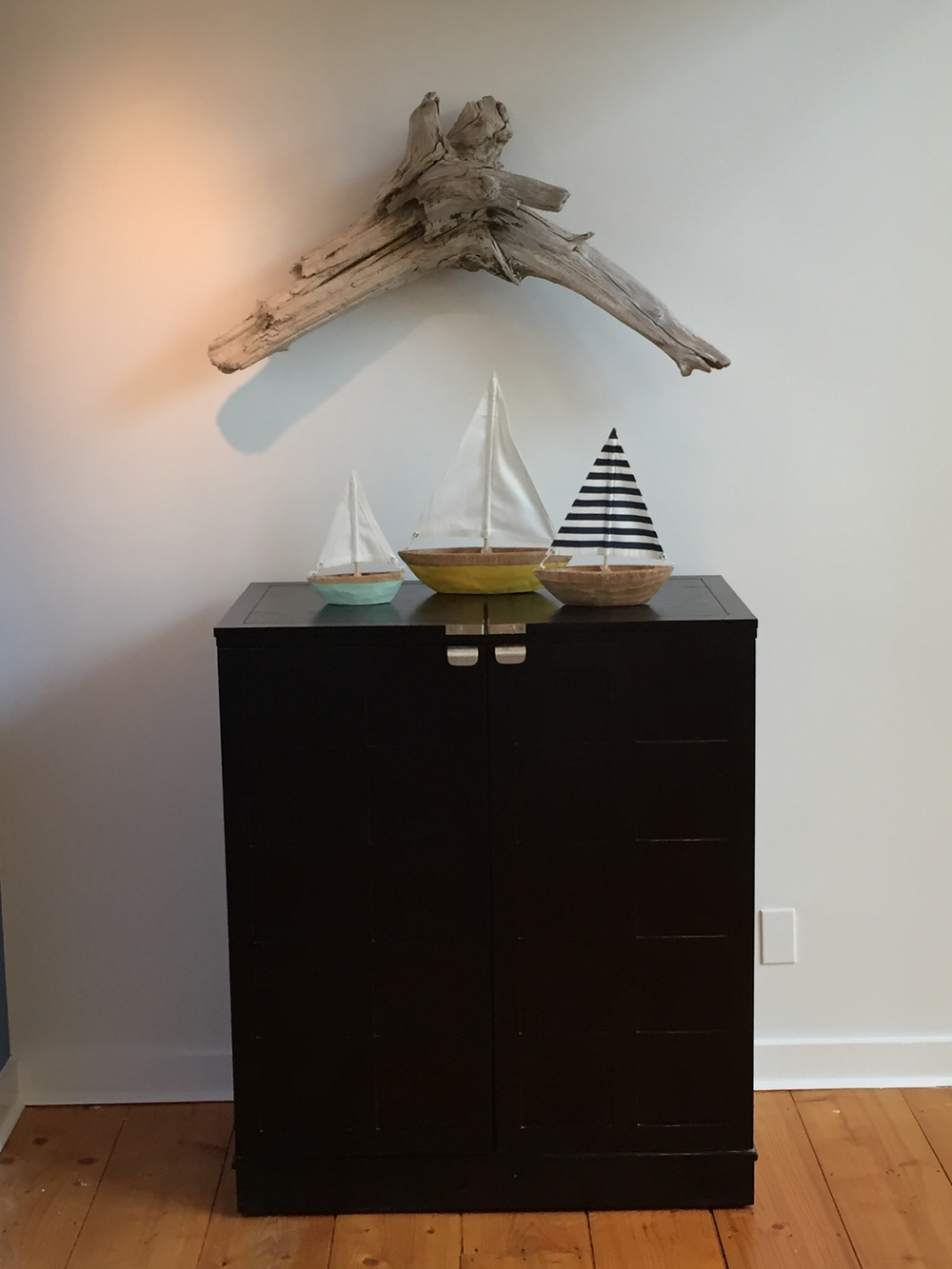 The homeowner's existing bar cabinet is softened by using a unique piece of driftwood that they found as artwork.  It is the perfect personal touch for the space.