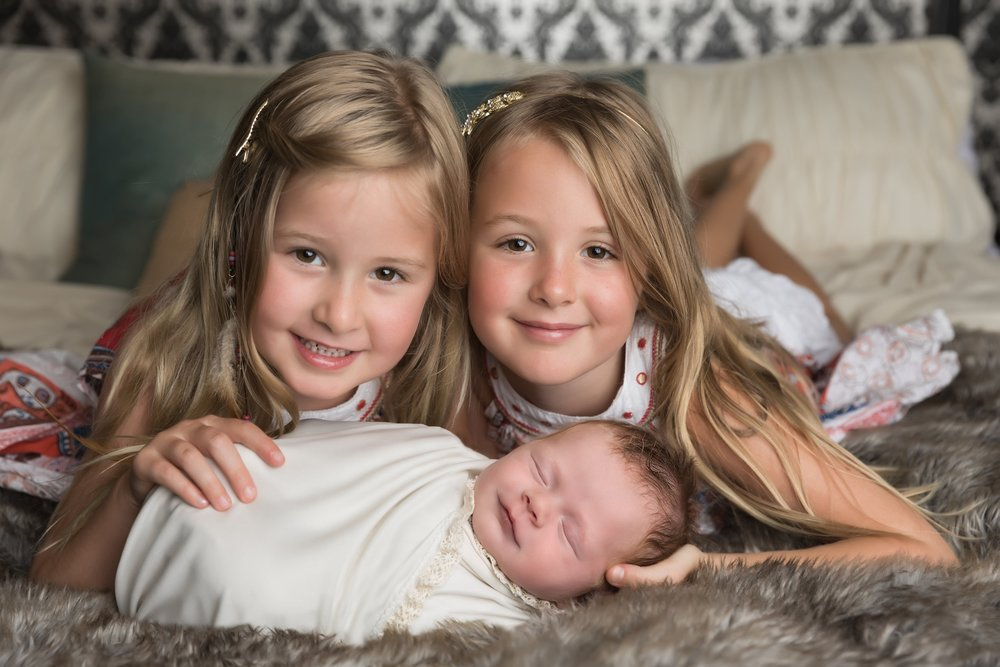 newborn girl with sisters.jpg