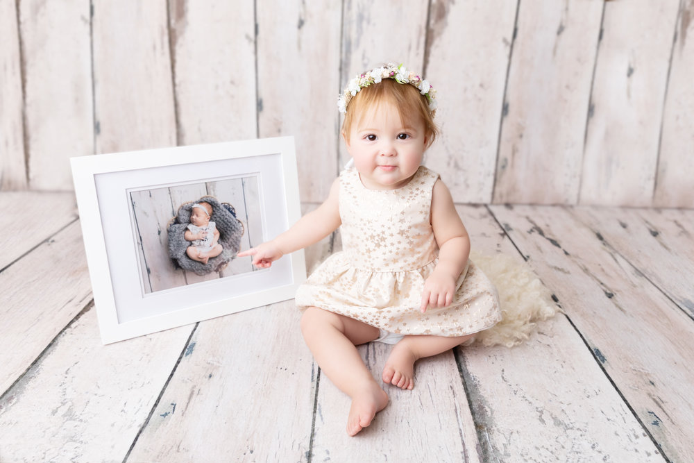 One year old with her newborn picture