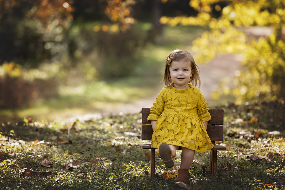 little girl on bench in autumn foliage