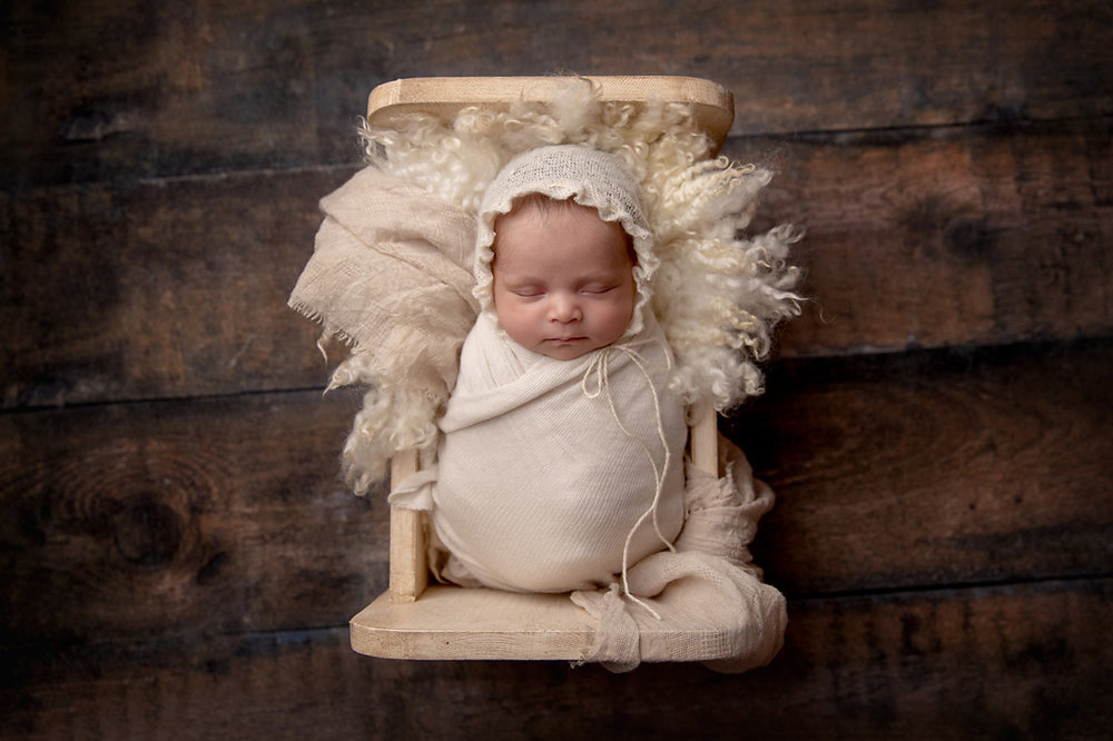 baby with bonnet in cradle