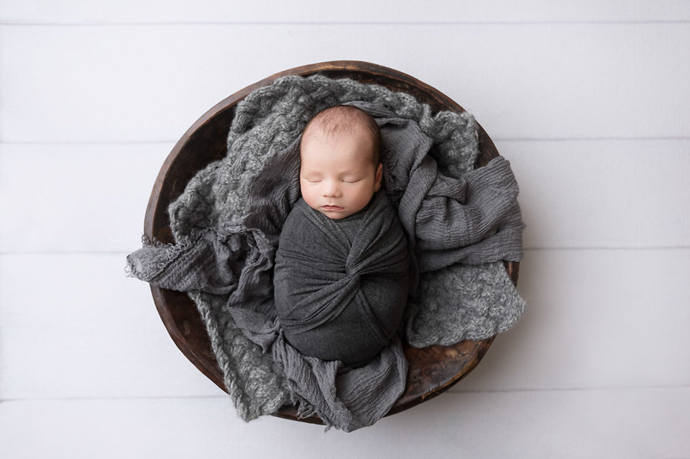 newborn boy in bowl