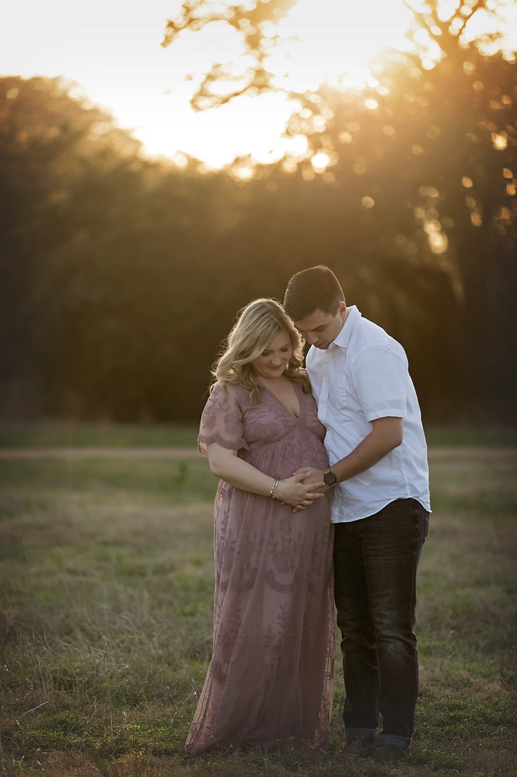 backlit sunset maternity couple