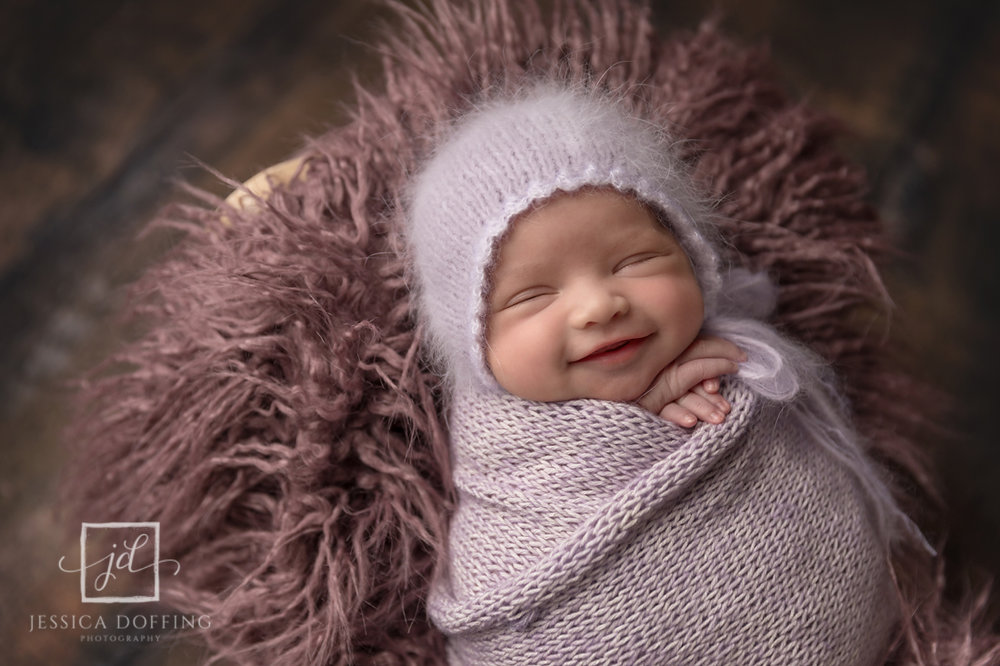 smiling newborn girl in purple