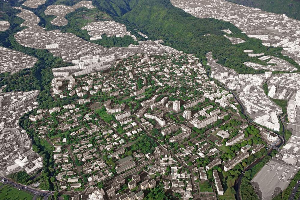 """Le quartier """"Camélias-Vauban-Butor"""" est l'un des quatre quartiers de Saint-Denis, inscrits en ZUS. Situé au Sud-Est de la commune, il est un quartier d'entre-deux : entre le centre-ville (à l'Est), les quartiers résidentiels des collines (eu Sud) et les secteurs d'équipements et d'activités (à l'Ouest); entre les ravines Butor et Laverdure; entre les collines et le littoral. Outre un habitat fortement dégradé, le quartier souffre d'un manque d'identité et de lisibilité des espaces publics.   Notre première mission de définition d'un plan guide a notamment permis :     - de mettre en cohérence et synergie les équipements et services en présence,     - d'asseoir le cœur vert familial au Sud dans sa vocation d'espace public de référence,     - de renforcer le cœur économique et historique que représente le Bd Mondon     - organiser un pôle le cœur de vie familiale au Nord dans les hauteurs du quartier, offrant enfin des équipements publics et des lieux de sociabilité."""