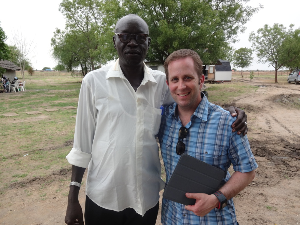 Scott Bowman (right) presents a tablet with the Health eVillages platform to Dr. Gai at Memorial Christian Hospital in Bor, South Sudan.