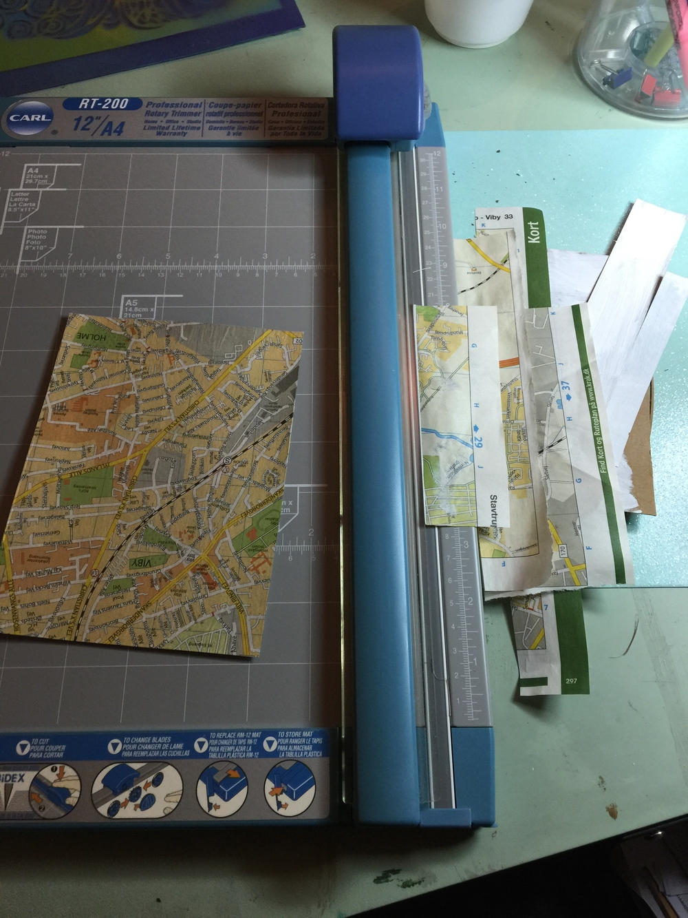 Glue the map to cardboard using a glue that will not leave the paper winkled when its dry.( decoupage, scrapbooking or archival glue) Examine the surface, smooth away wrinkles and gently wipe away any glue on the surface to make drawing easier. Trim excess paper.