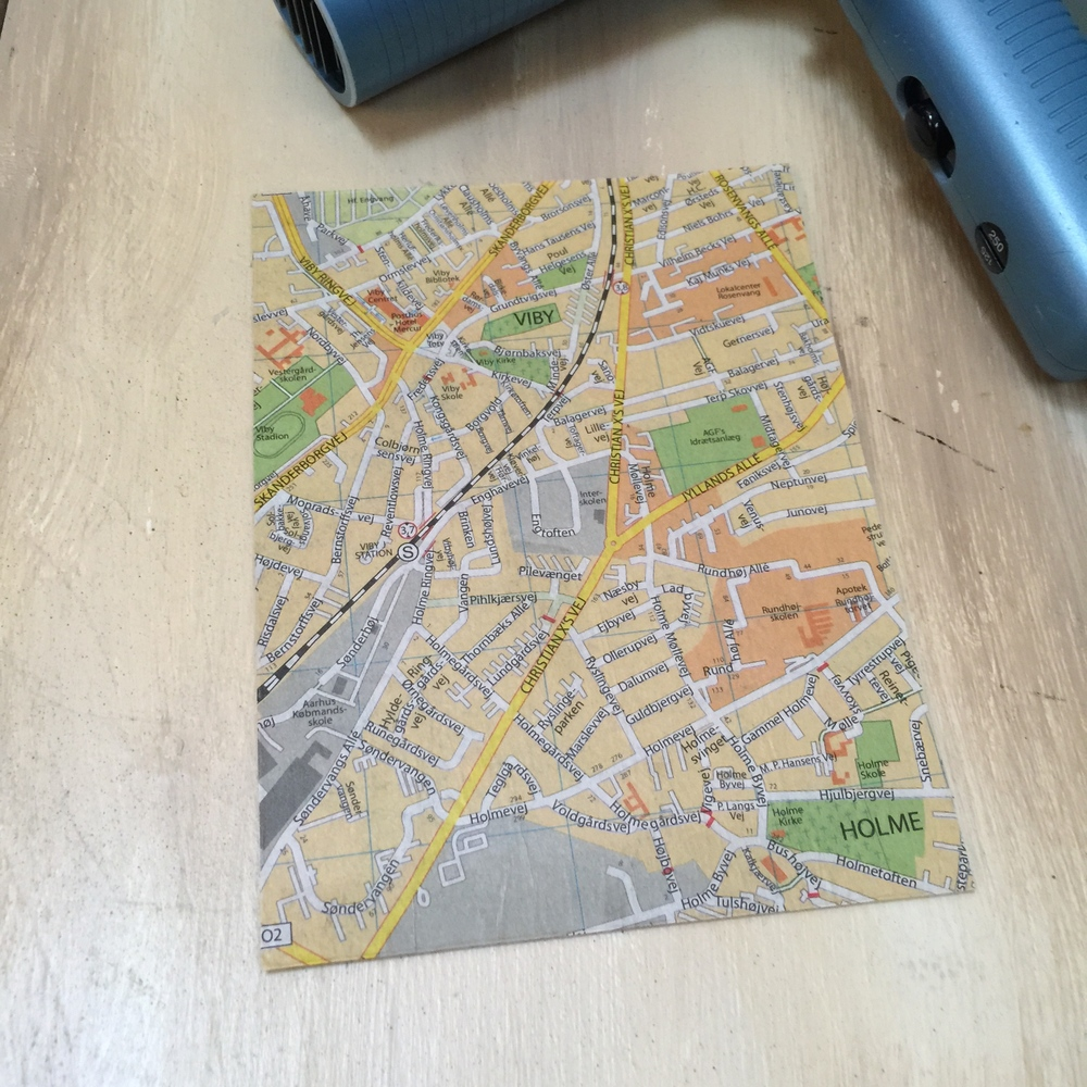 Now the map and its cardboard support is dry and ready to go. Look at the patterns in the map for ways to fit a face or features. if you are having trouble finding where to place it, lay tracing paper over the map and sketch out some possibilities.