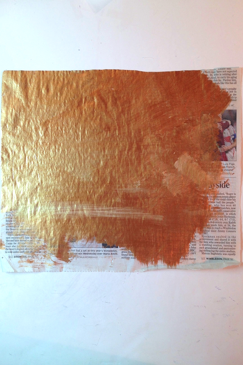 Clean your brush on newspaper and let it dry. The paint on this project is cooper and gold acrylic paint. Its randomly brushed on and some of the newspaper is purposely left unpainted to keep it raw looking.