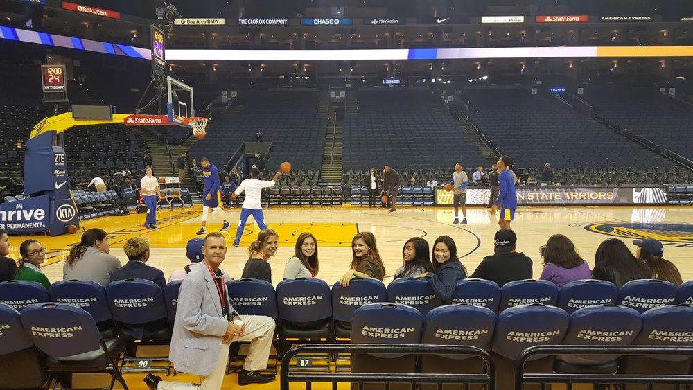 Dominican Professor Bradley Van Alstyne poses with students in their courtside seats at the Oracle Arena