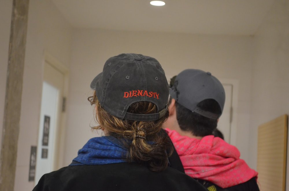 "A woman in line for the bathroom sports a hat featuring ""Die Nasty"" on the back - a reference to the phrase Nasty Woman, a popular saying within the Women's March movement."