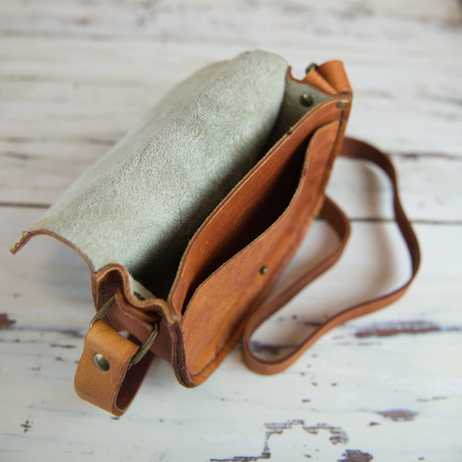 The crossbody purse includes a front pocket sized for phone storage.