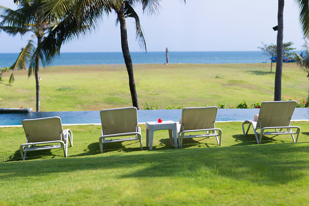 Sungai-Tinggi-Beach-Villa-Deckchairs-poolside-with-sea-view.jpg