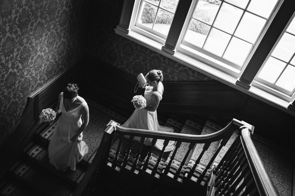Bridesmaids on the staircase at Brockencote Hall in Worcestershire.
