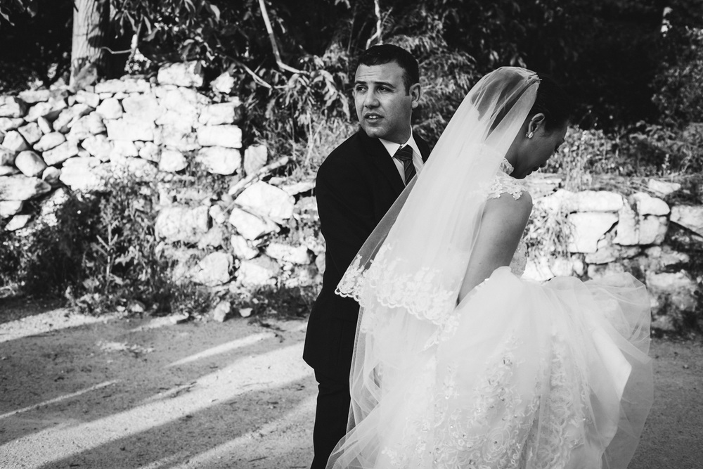 Bride and Groom walking through the street of a small village in Crete.