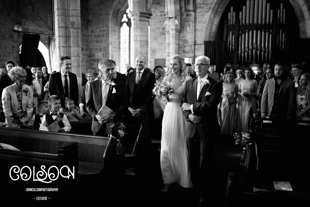 Bride walking down the aisle at a wedding in Leicestershire.