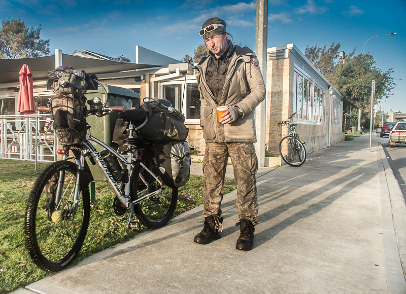 Scotty's life is loaded into canvas bags on the side of his bike. He says he has adapted the bike as he has travelled, adding extra comforts like solar panels to soften life on the road.
