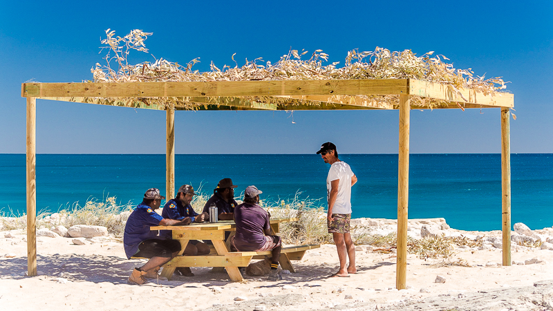 Tourist Shane admires a bough shed built by the rangers. The rangers have been building bough sheds at community beaches to facilitate a more enjoyable experience for tourists, and their fellow community members.