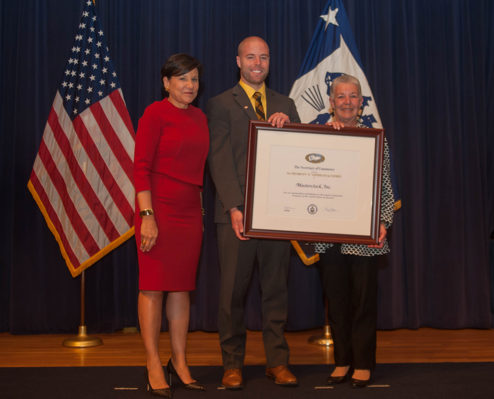 "U.S. Secretary of Commerce   Penny Pritzker presents CEO John Clark and Mary Clark of Masterclock with President's ""E"" Award at a ceremony in Washington, D.C. on May 16, 2016."