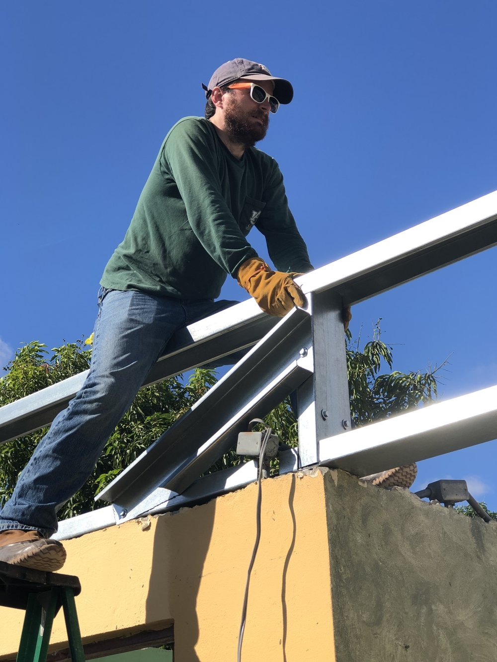 JT Mercer from Team 1 is shown here braving the highest part of a roof on the second story to hold down the support beams for what will be a new metal roof.