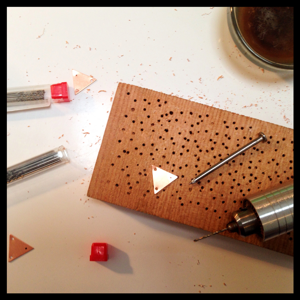 Drilling holes in copper triangles.