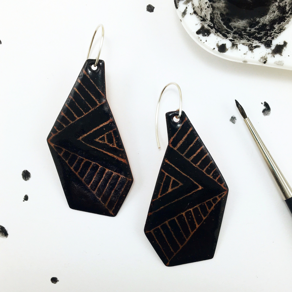 Today's creative experiment: Geometric enamel earrings with sgraffito in overglaze black over clear enamel that lets the copper beneath it shine through.