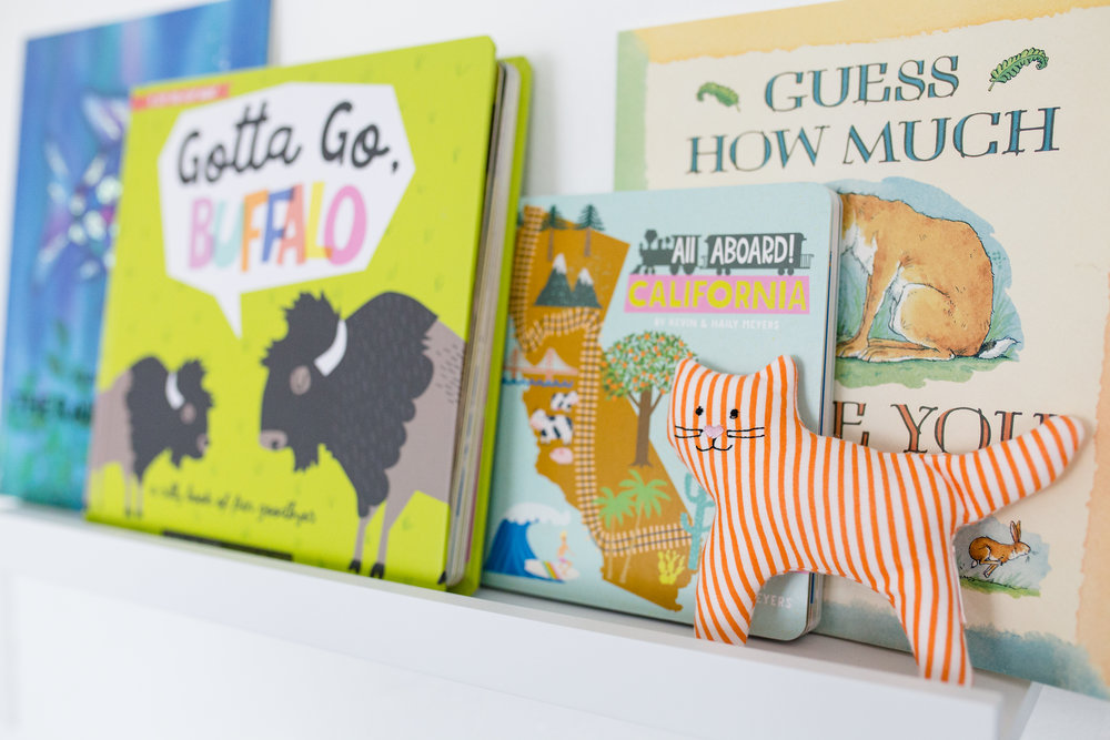Some favorite books to adorn her room and add color to the walls. (Orange [above] and Grey [below] cat rattles - Ikea)
