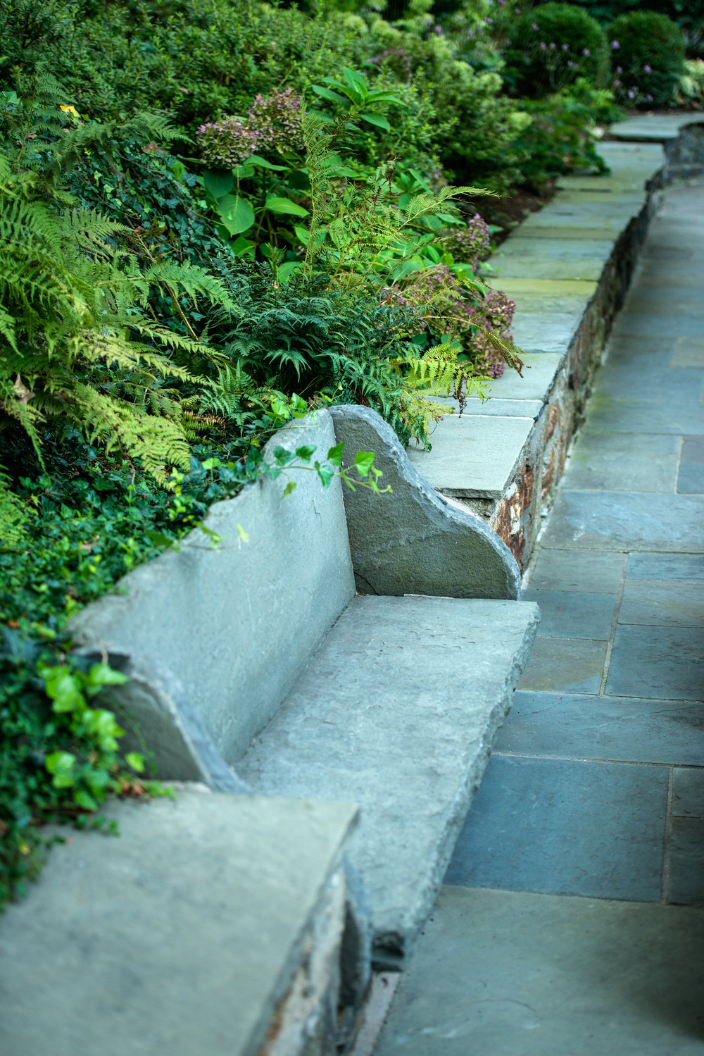 Natural stone bench built into garden wall structure