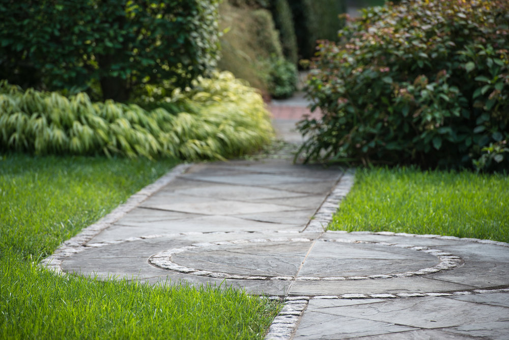 Cut flagstone walkway framed with granite cobble stone paver with circular detail