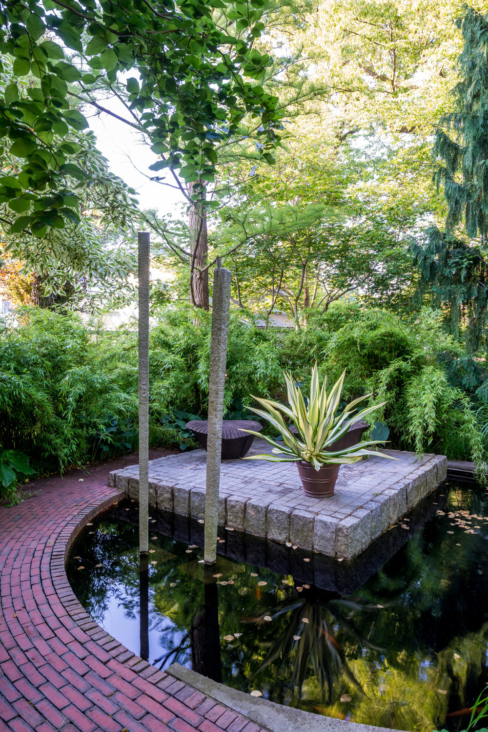 """Pond with """"floating"""" patio and stone columns"""