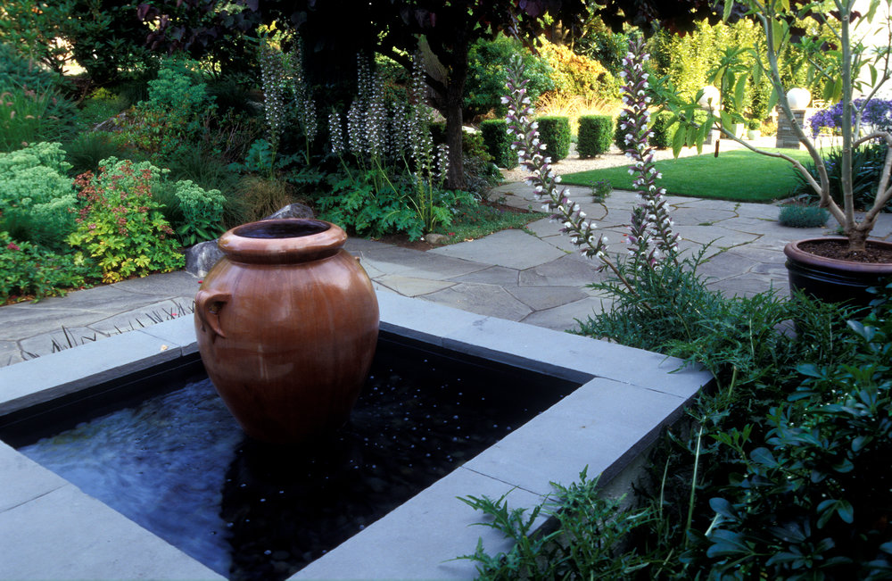 Here, an artful fountain and the sound of flowing water attracts and relaxes visitors in an outdoor garden room.