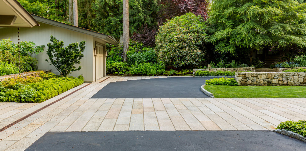 A good grading base makes blending materials like asphalt and stone beautiful and functional. Also, great curb detail where it steps down to meet grade at the stone band.
