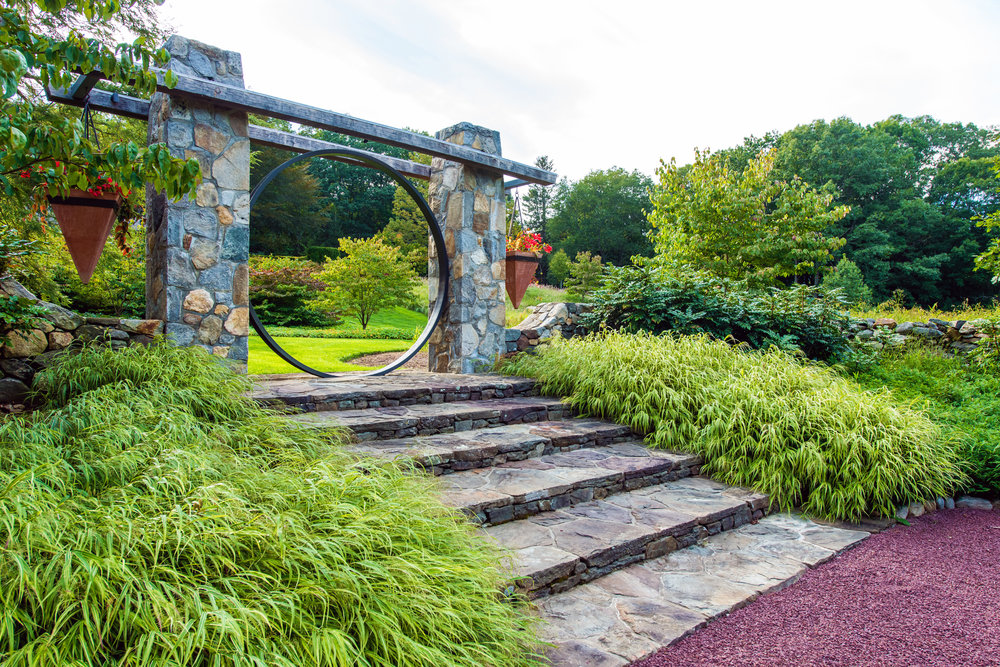 Stone gateway with circular element and hanging planters
