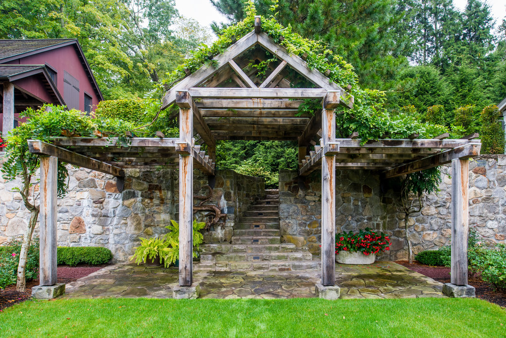 Wooden gateway arbor with stone walls and steps