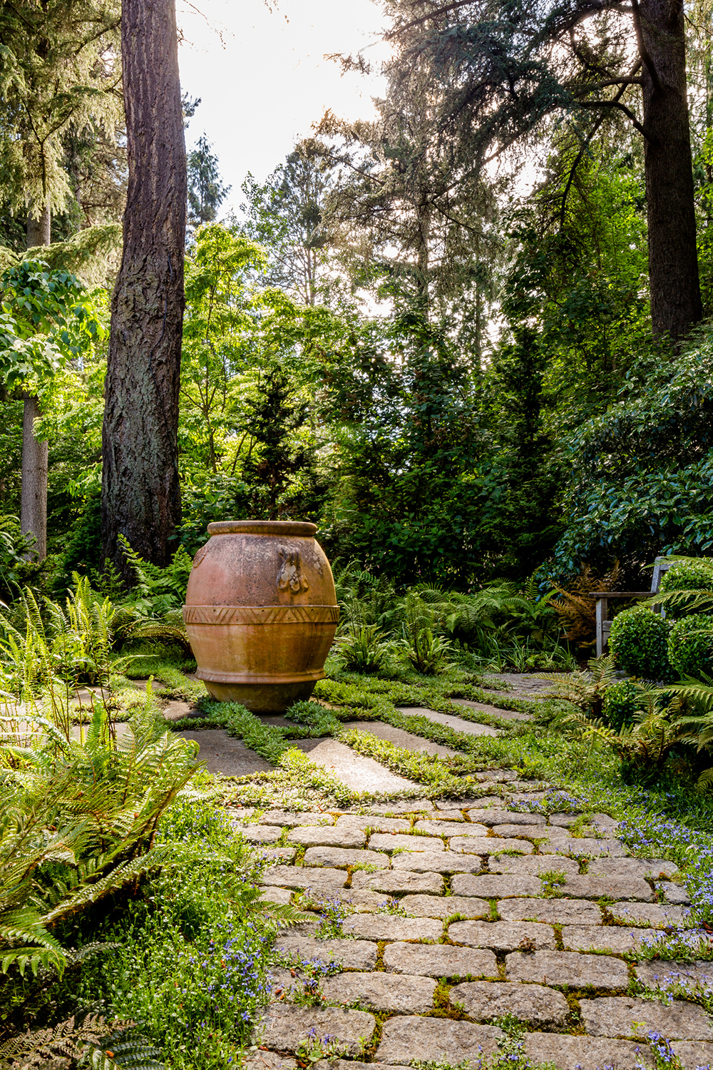 Borrowed view: the background trees are not on the property but help create a more expansive feel. The paving and pot add interest and draw the visitor to the small bench in back. Photo by    Miranda Estes Photography