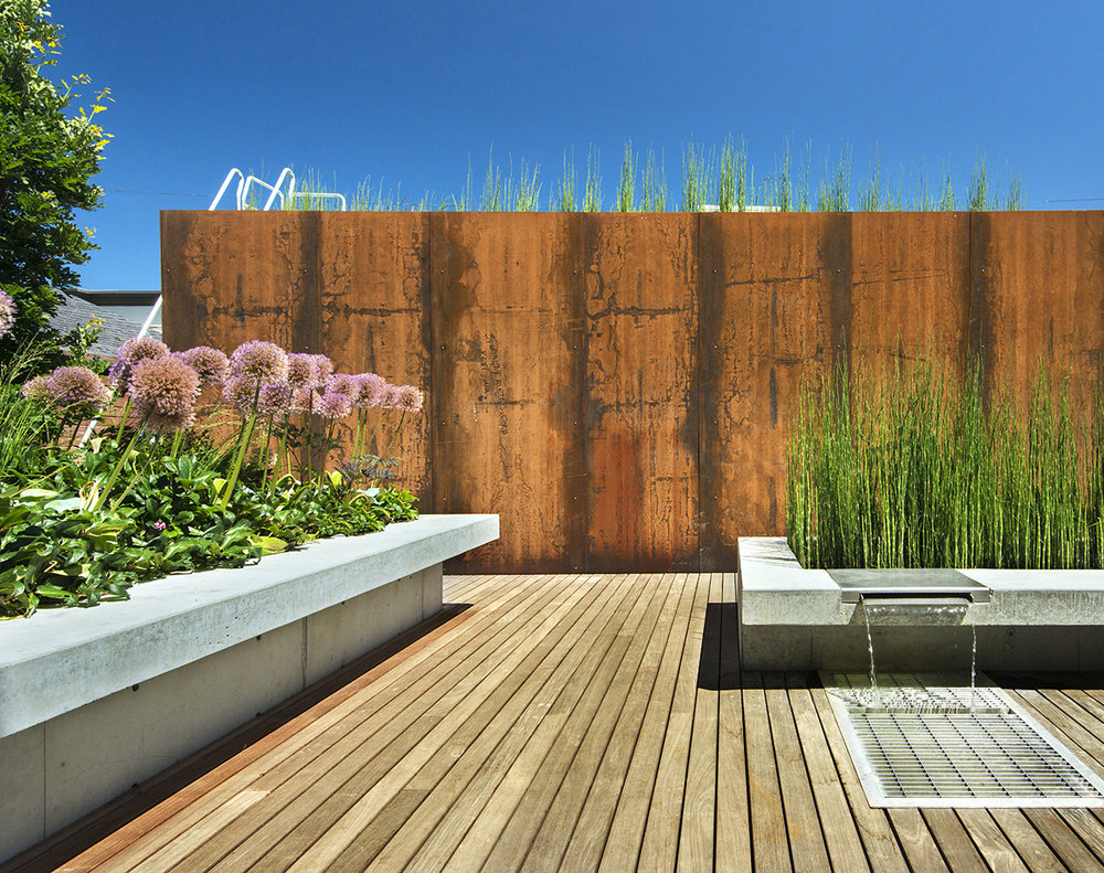 A large variety of materials can be used to create screening: this steel wall hides the garage and alley from view while tall plants on the sides screen neighbors in this small back yard.