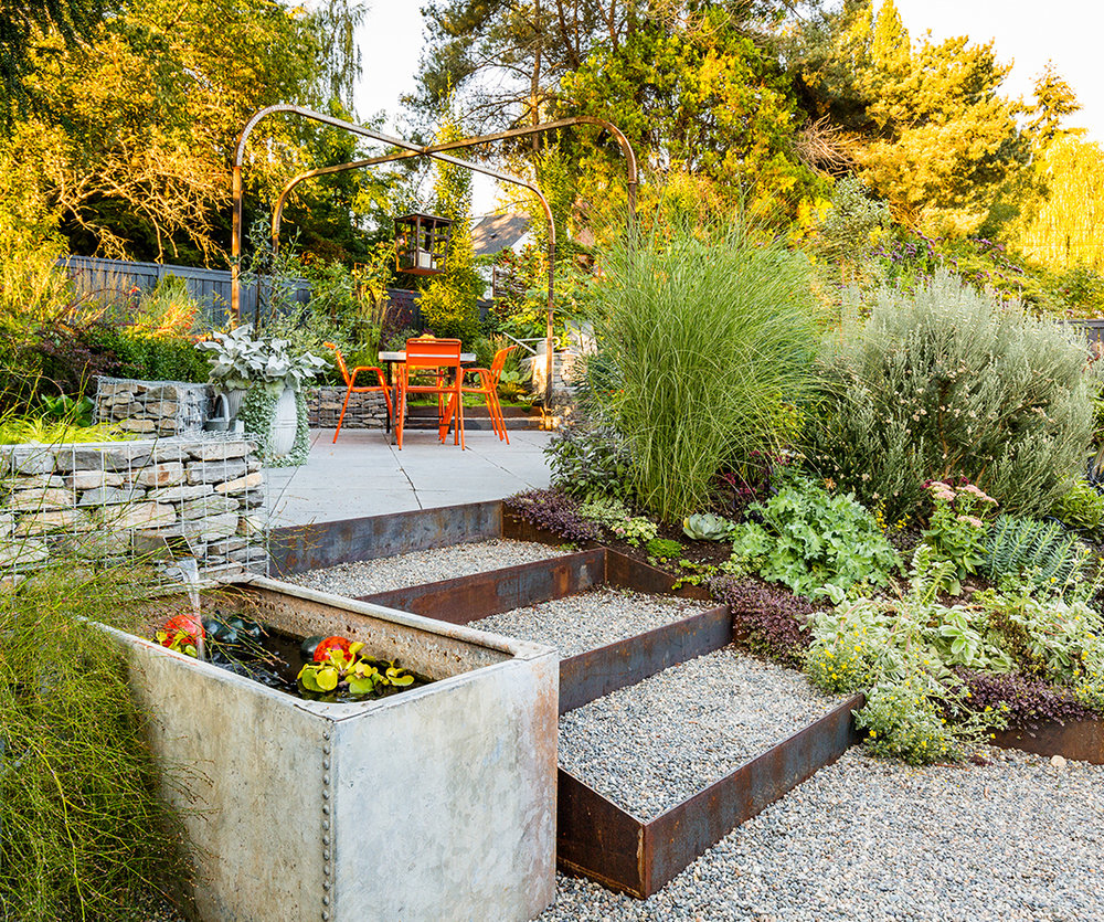 This small back yard is transformed with a variety of materials, plants, and furnishings that reflect the owner's vibrant character. Care was taken with every detail and a variety of pots and features can be swapped out to keep it feeling fresh. Photo by    Miranda Estes Photography