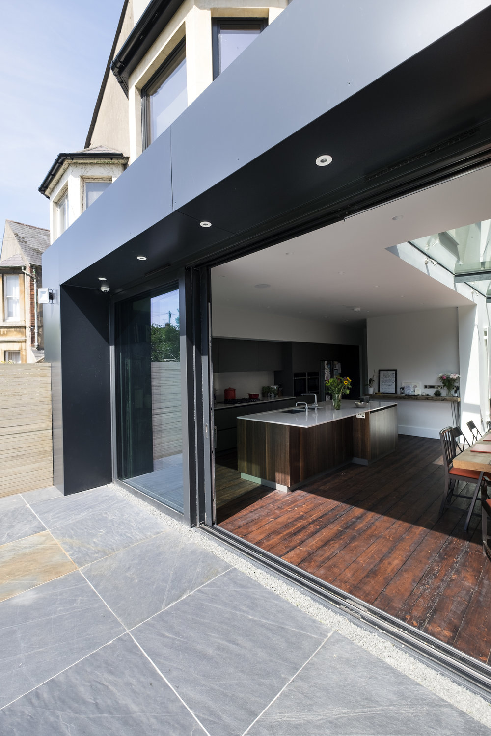 The dark grey Aluminium cladding, with full height lift and slide solar control glass doors, reclaimed stained timber floorboards and Welsh slate tiles, blend beautifully the outside with the inside ; the old and the new.  The existing Victorian architectural charm is retained with colours and textures of its time, whilst the additions unashamedly reflect the way we build today.