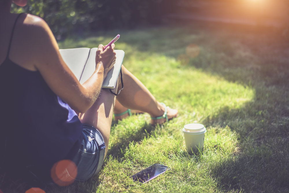 Closeup of a girl in a blue top and denim shorts takes notes in a notebook while sitting on the lawn. Next on the grass is a smartphone and is a cup of coffee.Bright sunlight, light effect.