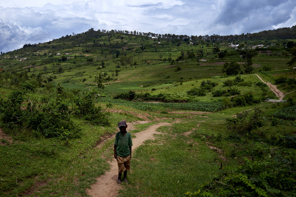 A young boy stands for a photo at the base of a valley among a few of the countless hills that sprawl across Rwanda.