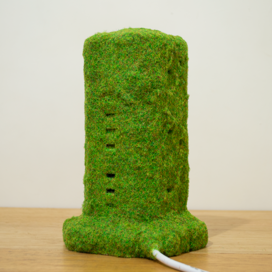 Disguised Office Infrastructure (WiFi Extender) , 2018, WiFi Extender, artificial grass, spray mount, 20 x 7 x 6 cm, Unique. Image courtesy of the artist