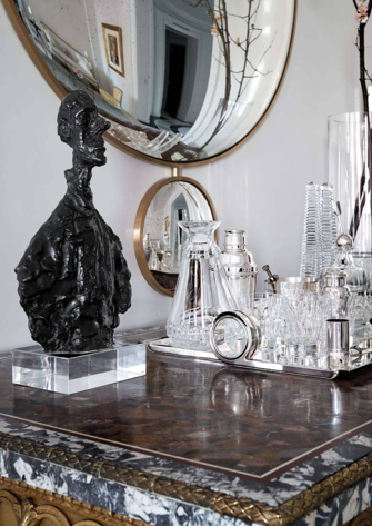Gorgeous moment in the living room. The antique Italian marble-topped console is topped with a sculpture by Alberto Giacometti and barware from Christofle.