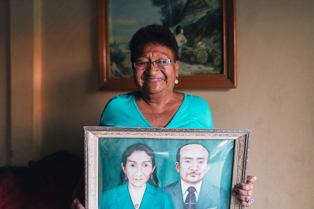 Marta posing with a portrait of her parents. She makes and sells clothing from her home, a business her parents started.